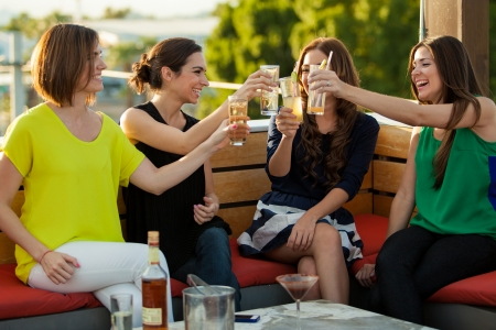 women having fun: Beautiful Latin female friends raising their glasses for a toast and having fun at a terrace Stock Photo