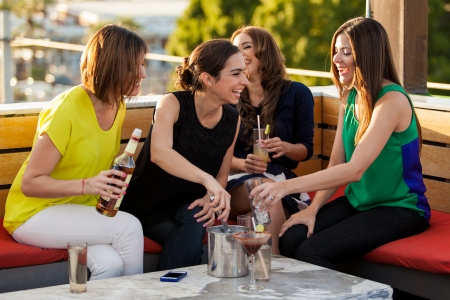 Group of four female friends having fun and drinking alcohol in a terrace in the afternoon Banco de Imagens