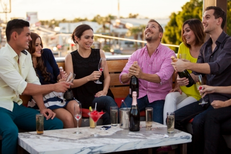 Group of Latin friends celebrating and popping a bottle of champagne at a terrace photo