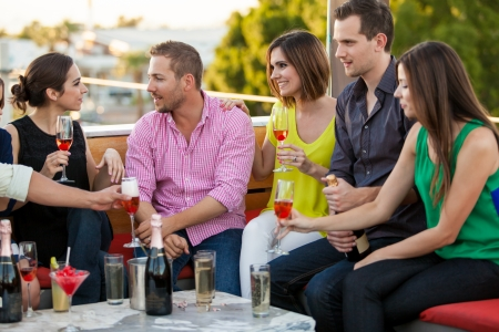 Large group of young adults hanging out at a bar and drinking champagne Stock Photo - 23562613