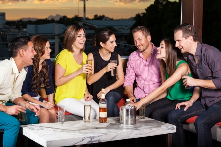 male friends: Group of young Hispanic adults having drinks in a terrace at sunset