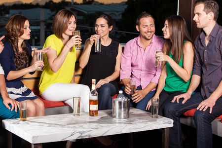 bar: Group of young adults drinking and talking in an outdoor bar at sunset Stock Photo