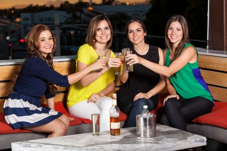 Beautiful female friends celebrating and toasting while having fun in a terrace at dawn Stock Photo - 23562637