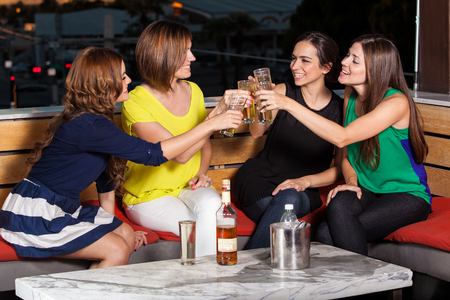 night out: Cute female friends having fun and drinks at a restaurant at night Stock Photo