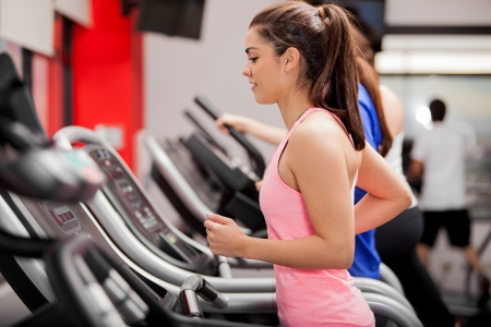 Cute young Latin woman exercising on a treadmill at a gym photo