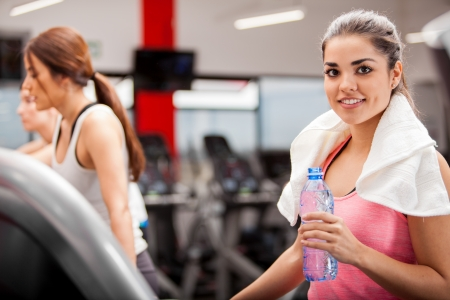 Cute Hispanic brunette relaxing and drinking water after a workout at the gym photo