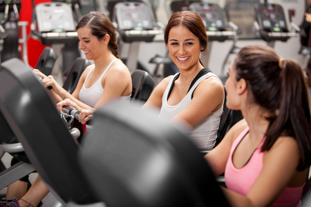 Group of cheerful female friends chatting and enjoying their spinning class in a gym photo