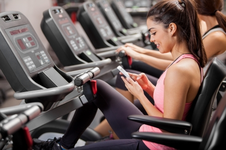 phone: Athletic young brunette social networking and texting during a spinning class at the gym