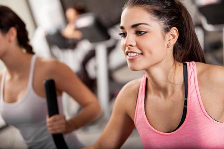 eliptica: Mujeres jóvenes Pretty Latina ejercicio en una elíptica entrenador en un gimnasio