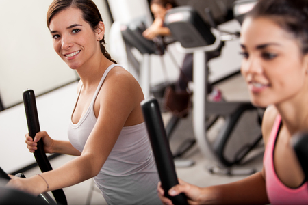 gym class: Cute young women taking a gym class in elliptical trainers Stock Photo