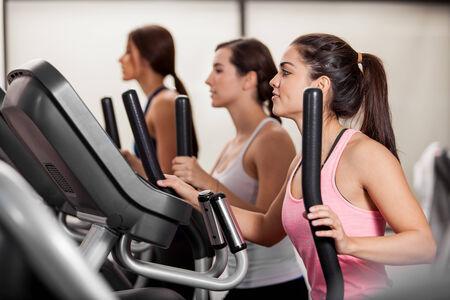 eliptica: Grupo de amigas haciendo algo de cardio en un entrenador elíptico en un gimnasio Foto de archivo