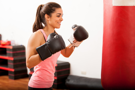 punching bag: Pretty Hispanic girl training box with a punching bag and a pair of gloves