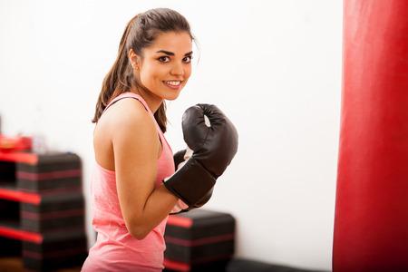 パンチング バッグの横にあるトレーニングとボクシング グローブを身に着けている若い美人 写真素材