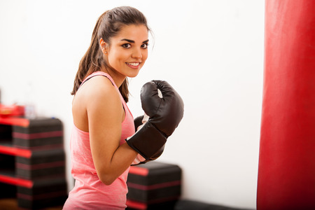 girl punch: Beautiful young woman training next to a punching bag and wearing boxing gloves Stock Photo