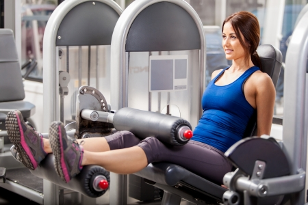 simulator: Cute young brunette building leg muscles in a simulator at the gym