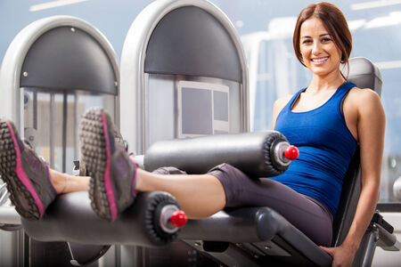 simulator: Pretty Hispanic brunette exercising in a simulator in a gym Stock Photo