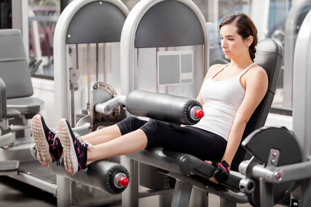 simulator: Cute young Latin woman doing a leg workout in a simulator at the gym