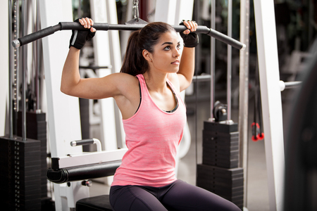 simulator: Cute Hispanic woman toning her muscles in a simulator at the gym