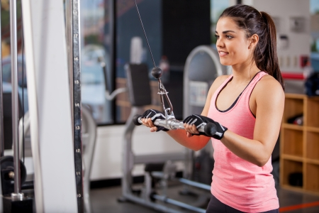 Pretty young woman using a pulley to tone her muscles in a gym Stock Photo