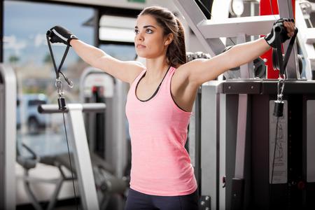 poleas: Hermosa morena utilizando poleas para tonificar sus músculos en el gimnasio