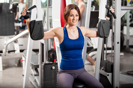 simulator: Cute young Latin brunette working out in a simulator at the gym