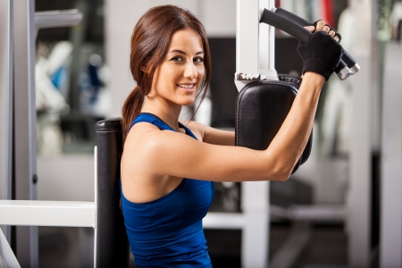 simulator: Pretty young brunette working in a simulator at the gym and smiling