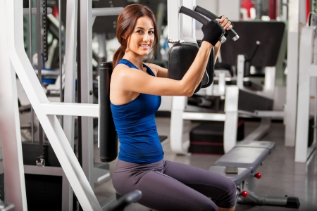 Pretty Latin young woman in a sporty outfit working out in a simulator in a gym photo