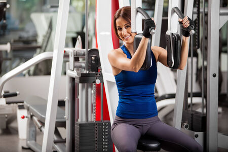 simulator: Beautiful Hispanic young woman working out in a simulator at a gym and smiling