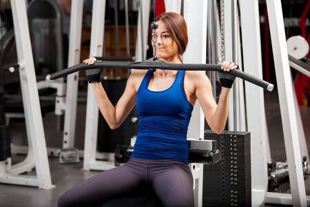 simulator: Pretty young athletic woman building some muscle in a simulator at the gym Stock Photo
