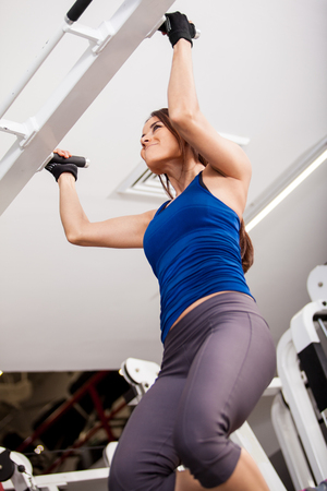 angle bar: Very athletic young woman doing some bar pull ups at the gym  Shot from a low angle