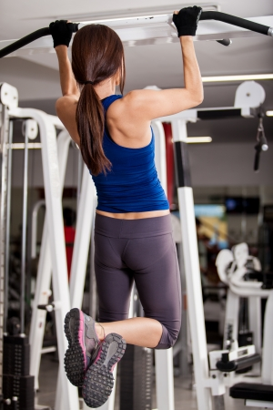 Pretty young brunette working out and doing some pull ups at a gym