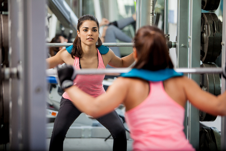 focusing: Pretty Latin brunette doing some squats with a barbell and focusing on her routine