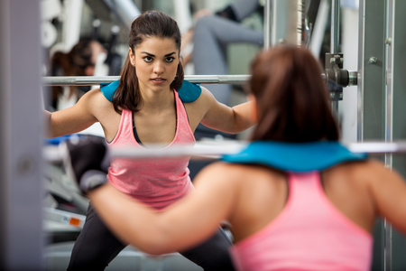 strong: Beautiful and strong woman concentrated on her workout routine by doing squats with a barbell Stock Photo
