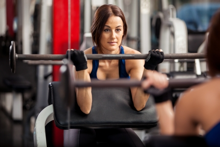 Pretty young woman lifting a barbell in front of a mirror at the gym