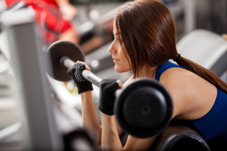 bicep: Pretty young woman concentrated in her workout and doing bicep curls in a bench at the gym