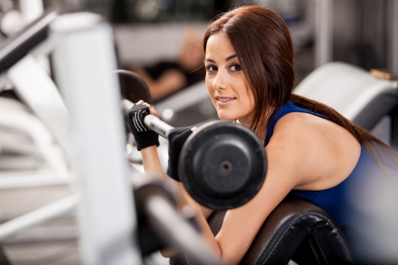 curls: Beautiful young Hispanic woman doing bicep curls at the gym and smiling