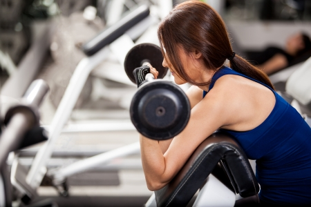 curls: Cute young woman working out by doing bicep curls in a bench at a gym