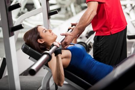 Persoonlijke trainer helpen van een jonge vrouw tillen een halter tijdens het werken in een sportschool
