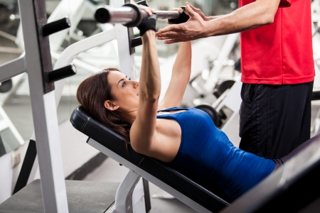 male chest: Cute young woman lifting a barbell with the help of a personal trainer in a gym