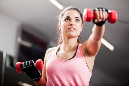 weight loss woman: Pretty brunette working out with some dumbbells in a gym