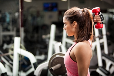 Gorgeous young woman using dumbbells to work on her triceps  Lots of copy space photo