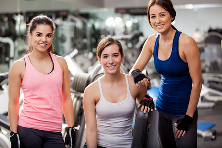 Three beautiful young women wearing sporty outfits hanging out at the gym photo