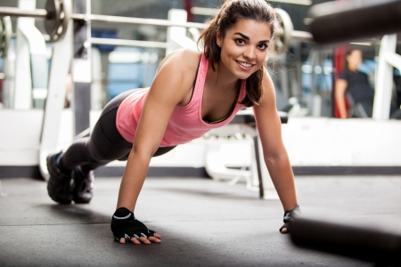Happy young Hispanic woman doing some push ups and working out at the gym Foto de archivo