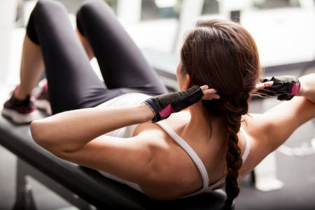 crunches: Young brunette doing some crunches on a bench in the gym before lifting weights Stock Photo