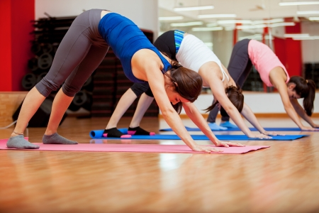 downward: Pretty young women trying the downward facing dog pose in yoga class