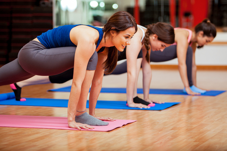 adult class: Beautiful young Hispanic women working out and enjoying their yoga class in a gym