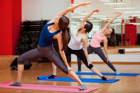Prachtige jonge vrouwen het beoefenen van yoga en het uitvoeren van een uitgebreide kant hoek vormen