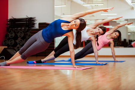 indoors: Group of three young women practicing the side plank pose during yoga class in a gym Stock Photo