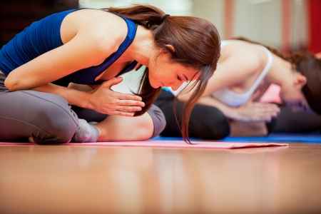 indoors: Group of young women relaxing and meditating during their yoga class in a gym Stock Photo