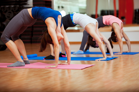 indoors: Group of young Latin women warming up and stretching at their yoga class